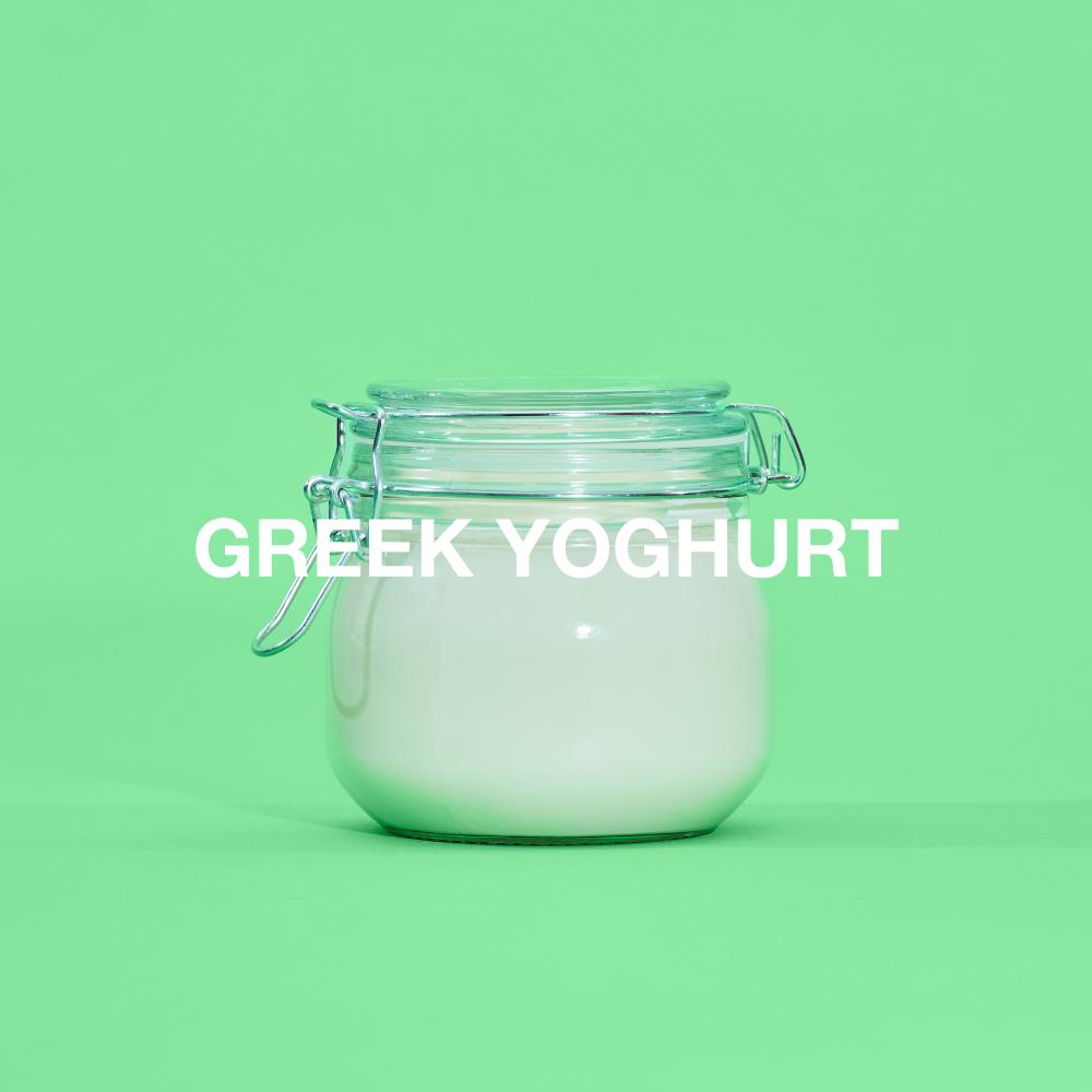 Greek yoghurt in a glass jar against green background
