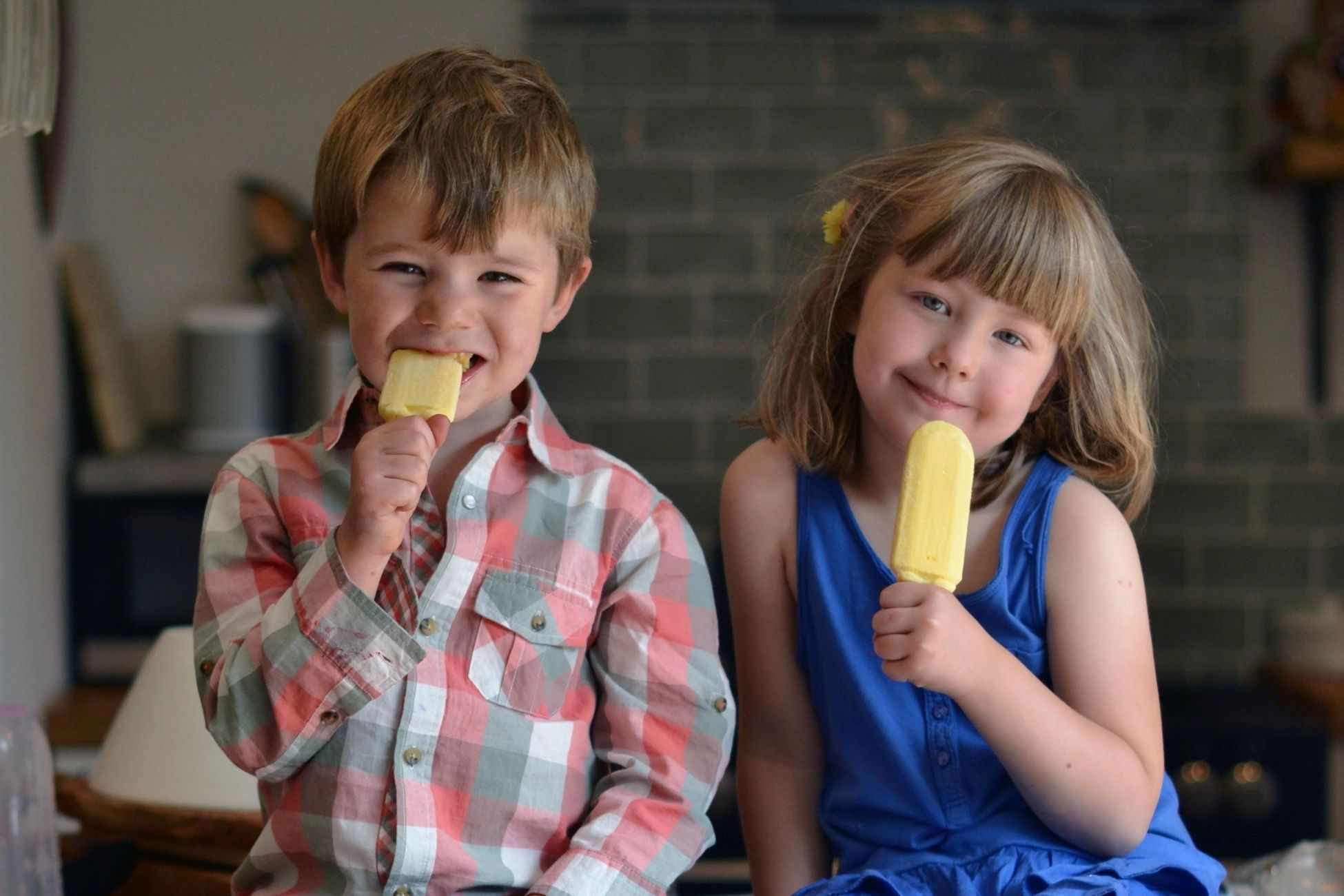 Two young children eating ice lollies in a kitchen