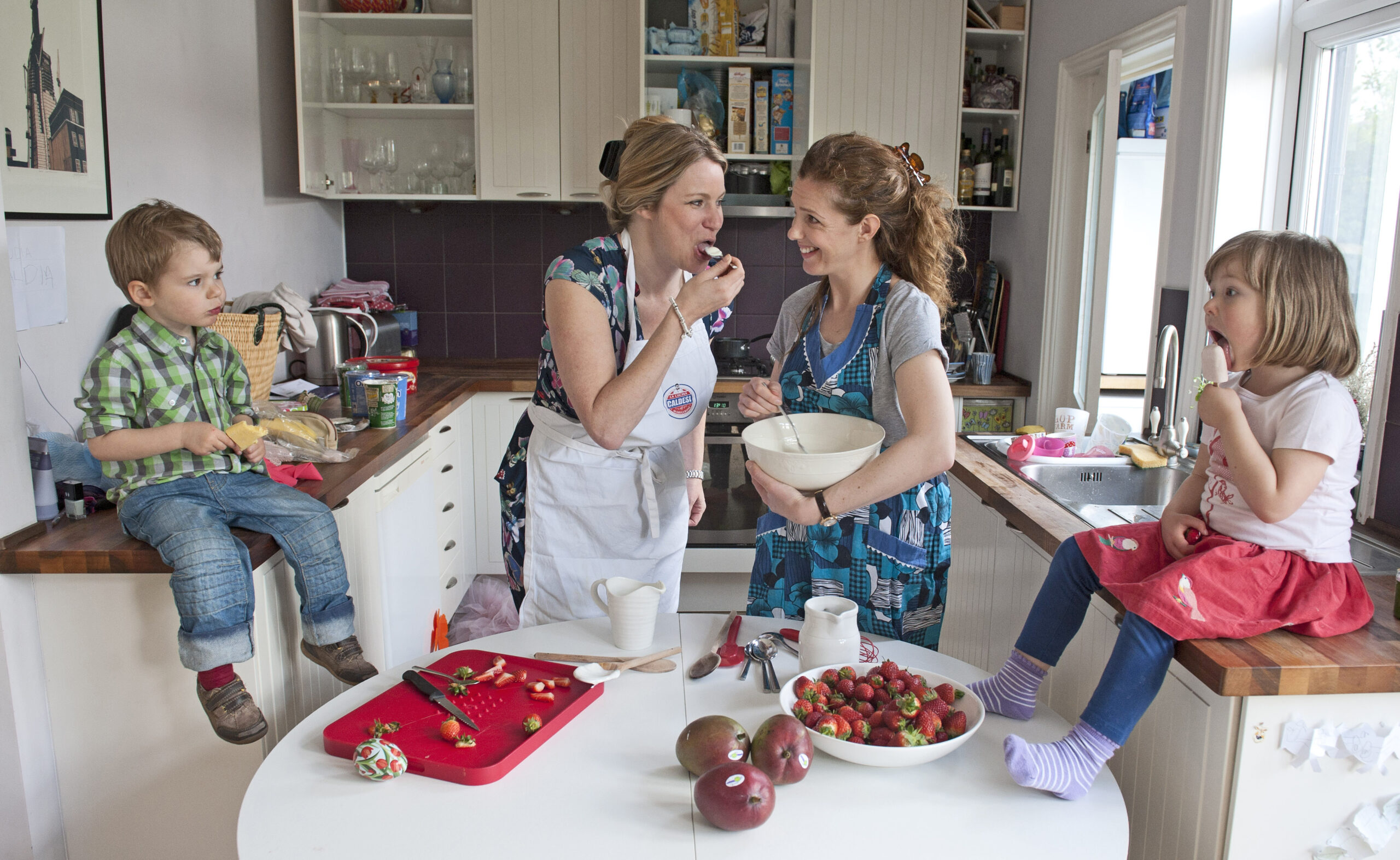 Two mums in a kitchen making lollies with their children