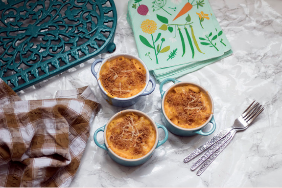 Three small macaroni cheese dashes on a table with napkin