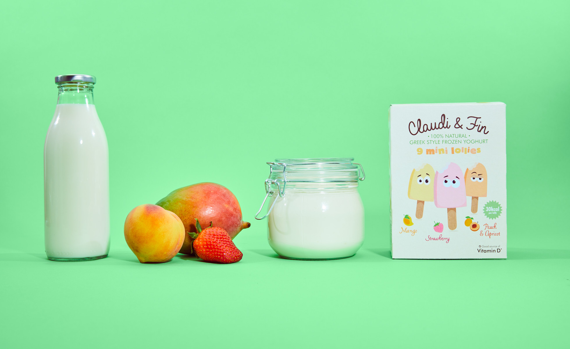 Milk fruit yoghurt and a box of lollies against a green background