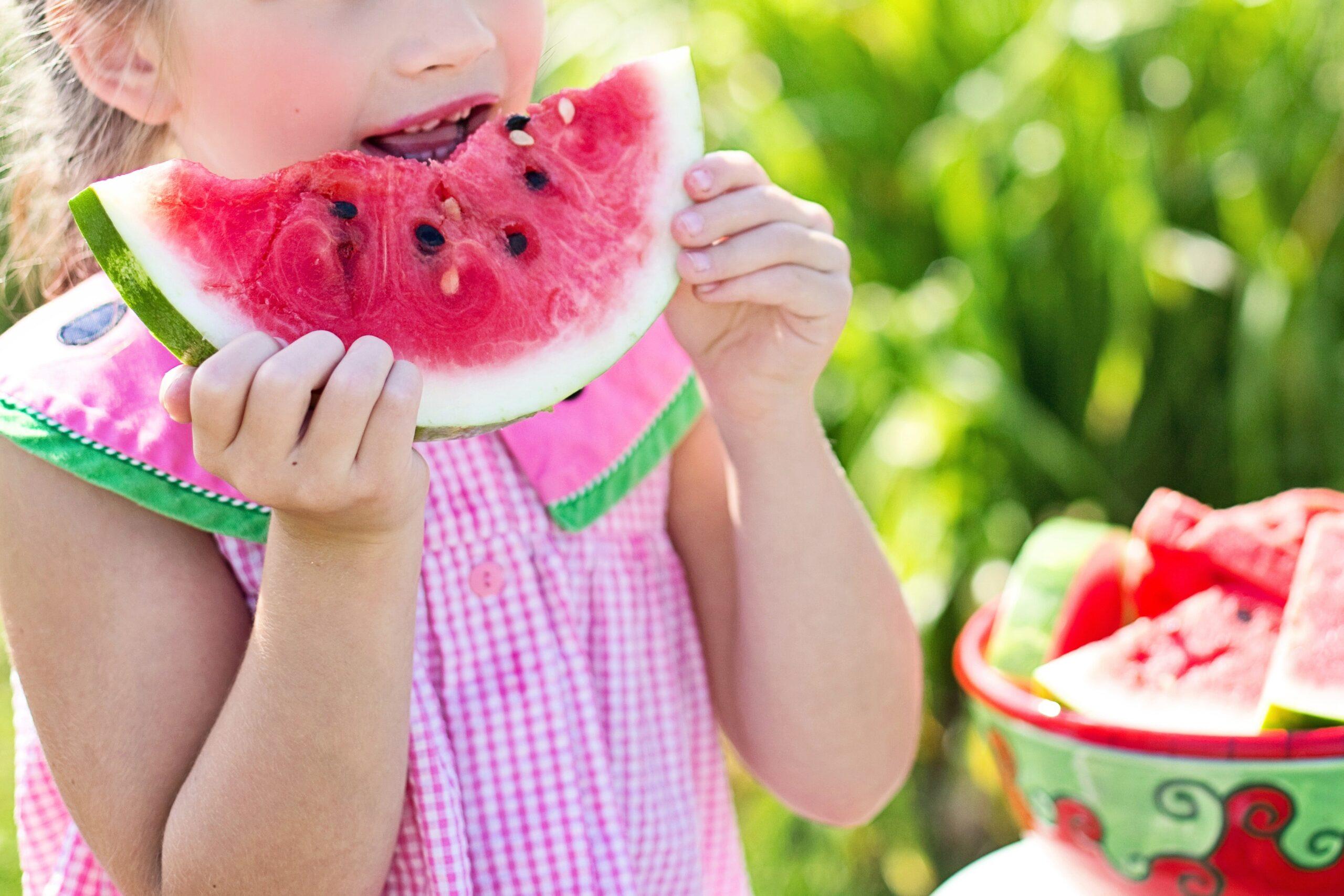 Little girl eating a watermelon outside