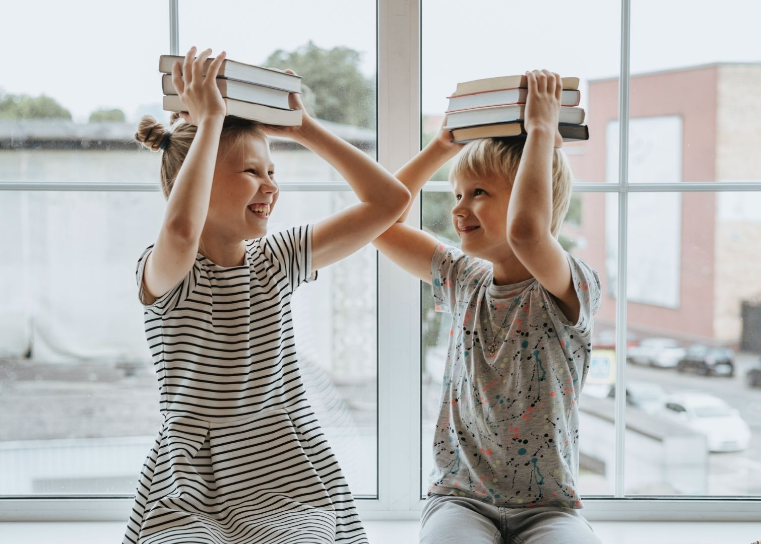 Picture of young boy and girl with books on their heads
