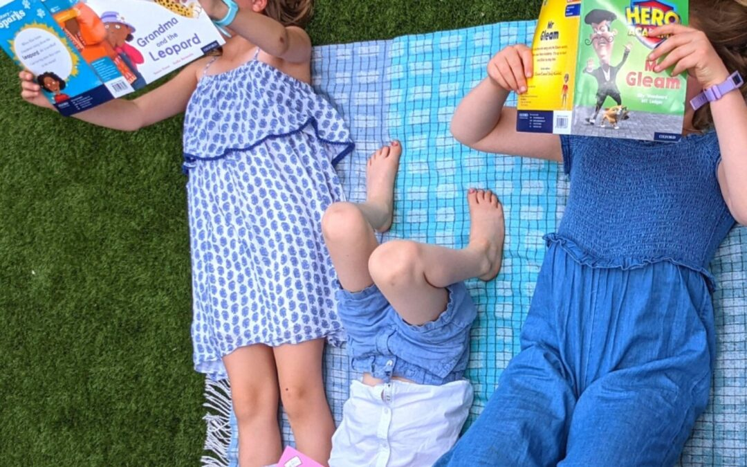 Three young children lying on a picnic blanket reading books