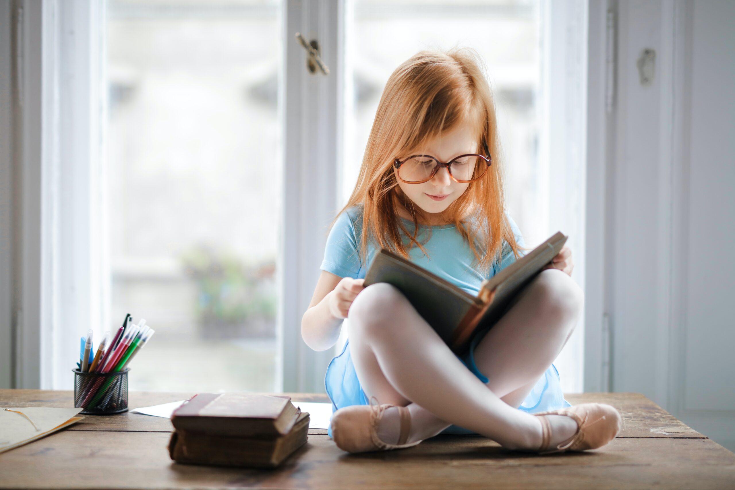 Little girl sat in a window reading a book