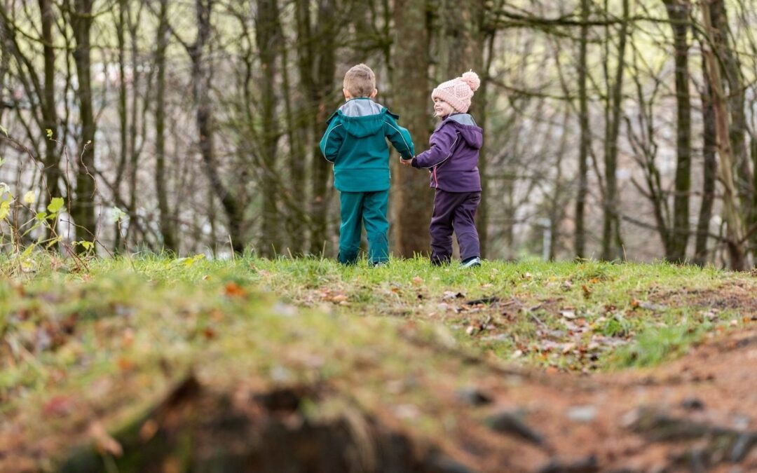 two young children in hats and outdoor clothes outside in the woods